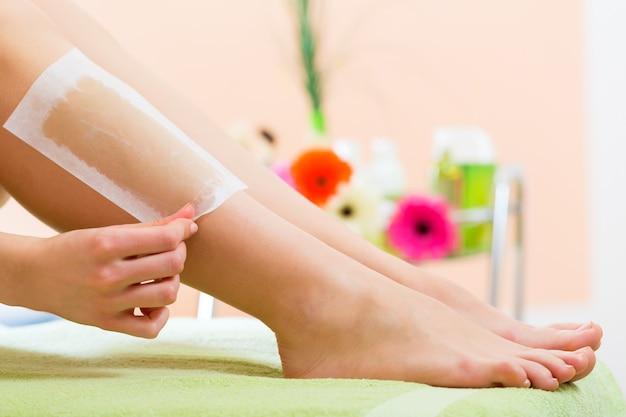 Mujer en spa encerándose la pierna