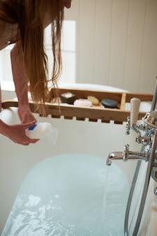 Mujer de spa hermosa mujer en el baño. la niña agrega espuma al baño en un baño completo.