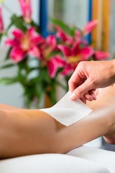Mujer en spa recibiendo depilación de piernas