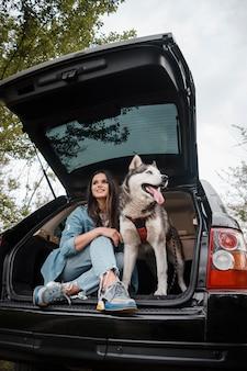 Mujer con su adorable husky viajando en coche