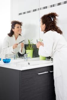 Una mujer en su baño mirándose la cara mientras se lima las uñas