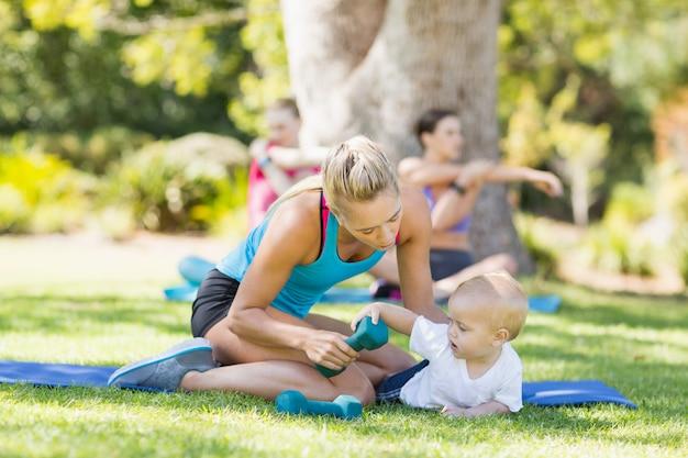 Mujer con su bebé mientras hace ejercicio