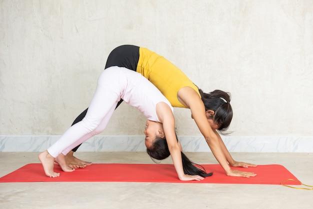 Mujer y su encantadora hijita haciendo yoga