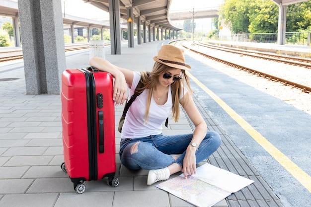 Mujer y su equipaje mirando un mapa