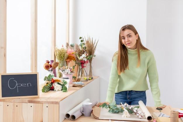 Mujer en su florería abriendo pronto