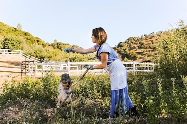 Mujer y su hija cosechando vegetales en el campo.
