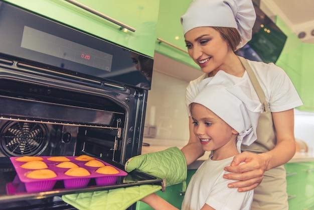 Mujer y su linda hija están horneando muffins en el horno