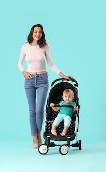 Mujer y su lindo bebé en cochecito sobre superficie de color