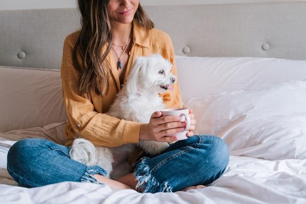 Mujer y su lindo perro en casa bebiendo té