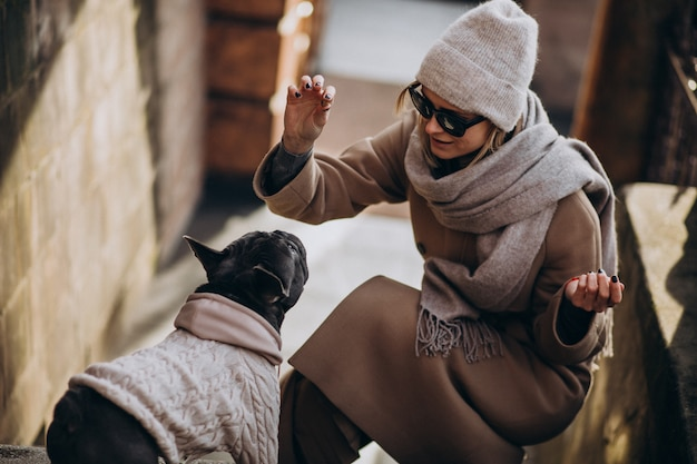 Mujer con su mascota bulldog francés saliendo
