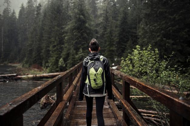 Mujer con su mochila de pie en el puente de madera