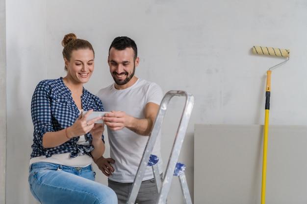 Mujer y su novio están mirando fotos por teléfono. están sentados en una escalera de mano, junto a un rodillo.