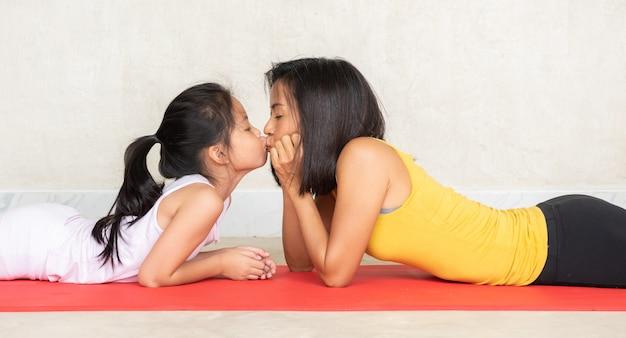 Mujer y su pequeña hija encantadora en estera de yoga