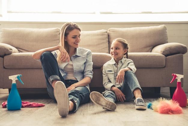 Mujer y su pequeña hija linda están sentados en el suelo.