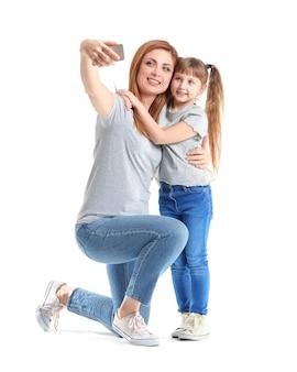 Mujer y su pequeña hija tomando selfie en blanco