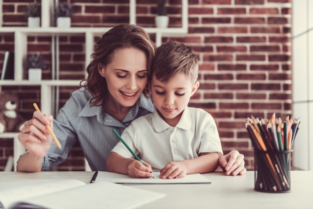 La mujer y su pequeño hijo lindo están dibujando y sonriendo.