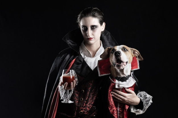 Mujer y su perro en disfraces de vampiro similares para halloween. hembra joven con vaso de bebida roja y su mascota cachorro vestida con el mismo traje de drácula
