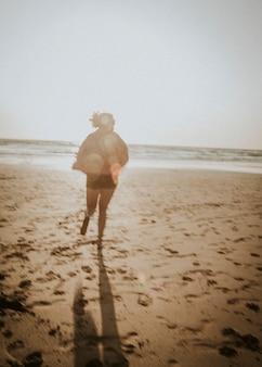 Mujer y su perro jugando en la playa.