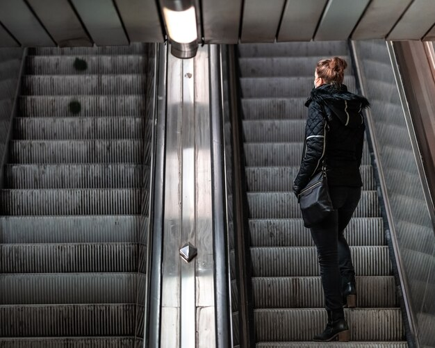Mujer sube por una escalera mecánica en el metro