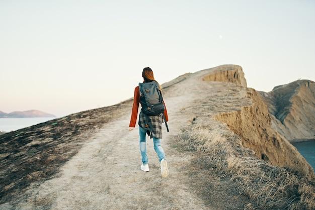 Mujer subiendo las montañas a lo largo de la carretera cerca del mar