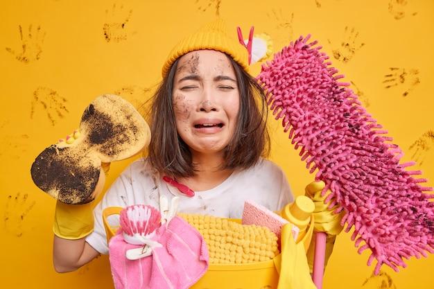 Mujer sucia angustiada se siente con exceso de trabajo después de pasar todo el día en poses de limpieza con esponja y la esponja expresa poses de emociones negativas contra la pared amarilla