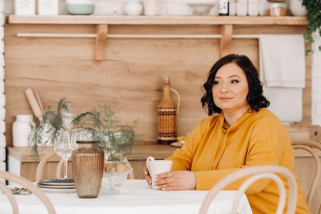 Una mujer con una sudadera con capucha naranja está sentada en una mesa en la cocina tomando café.