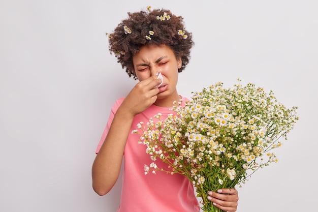 La mujer se suena la nariz con un pañuelo siendo alérgica a las flores de manzanilla sufre de hinchazón de ojos rojos y llorosos aislados en blanco