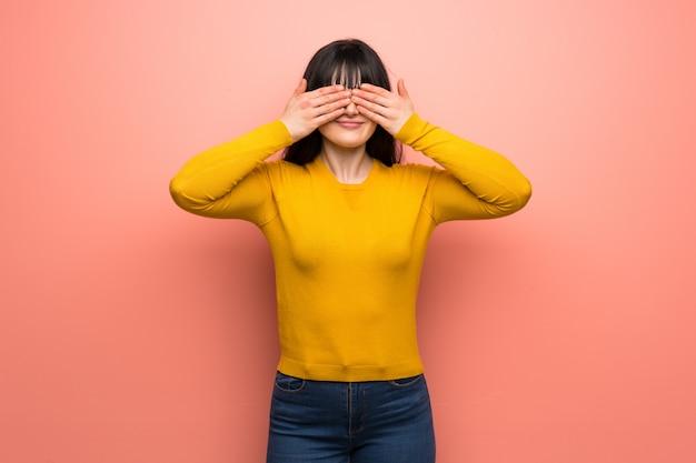 La mujer con el suéter amarillo sobre la pared rosada que cubre ojos por las manos. sorprendido de ver lo que viene por delante.