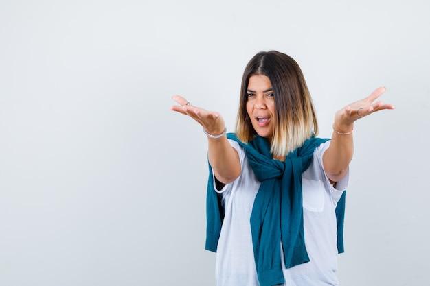 Mujer con suéter atado abriendo los brazos para un abrazo en camiseta blanca y mirando feliz. vista frontal.