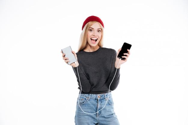 Mujer en suéter con banco de energía y teléfono inteligente