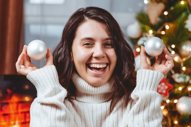 Mujer en suéter blanco posando cerca del árbol de navidad retrato