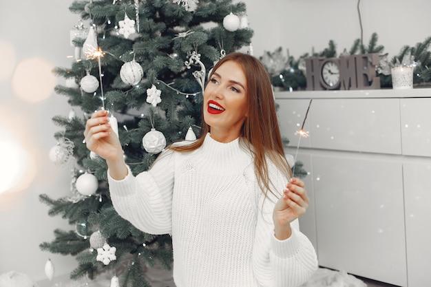 Mujer con un suéter blanco sentada junto al árbol de navidad