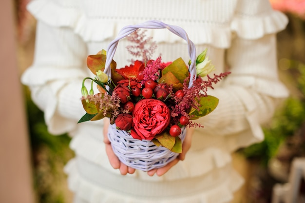 Mujer en un suéter blanco sosteniendo una linda canasta de mimbre con composición de flores de san valentín