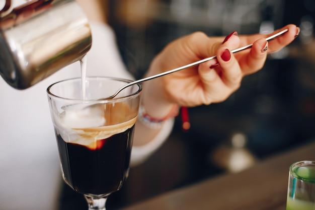 Mujer en un suéter blanco vertiendo leche en el postre de café