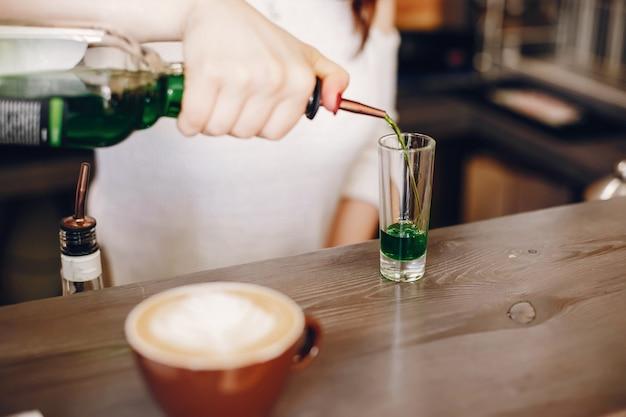 Mujer en un suéter blanco vertiendo syrop verde en vidrio