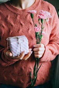 Mujer en suéter coralino que sostiene la caja de regalo y las hojas verdes frescas y las flores rosadas florecientes