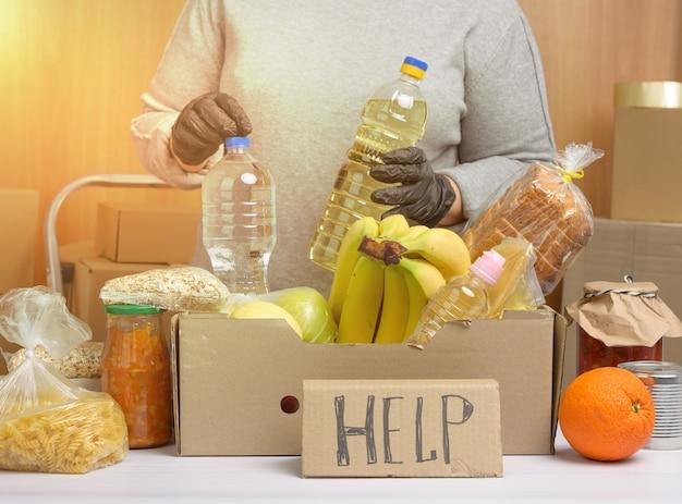 Mujer con un suéter gris está empacando alimentos en una caja de cartón, el concepto de asistencia y voluntariado, donación