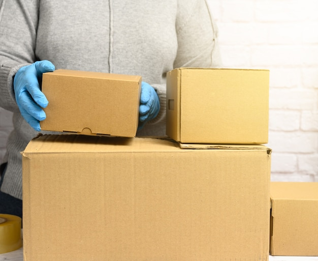 Mujer con un suéter gris está empacando y guantes azules sostiene una pila de cajas de cartón marrón, mudanza, donación
