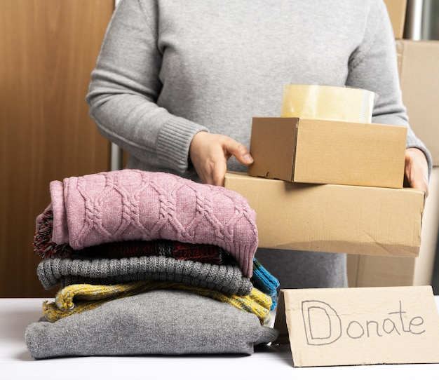 Mujer con un suéter gris está empacando ropa en una caja, el concepto de asistencia y voluntariado, de cerca