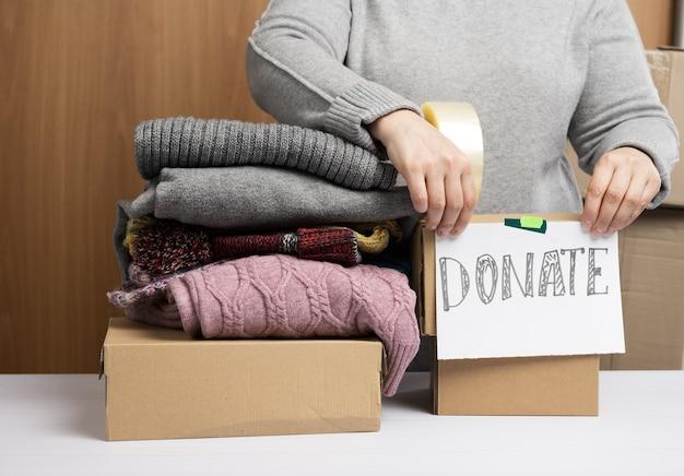 Mujer con un suéter gris está empacando ropa en una caja, el concepto de asistencia y voluntariado, donación