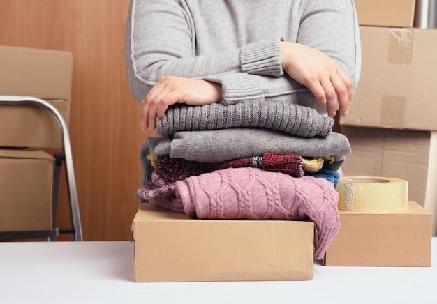 Mujer con un suéter gris está empacando ropa en una caja, el concepto de asistencia y voluntariado, en movimiento. vendiendo cosas innecesarias
