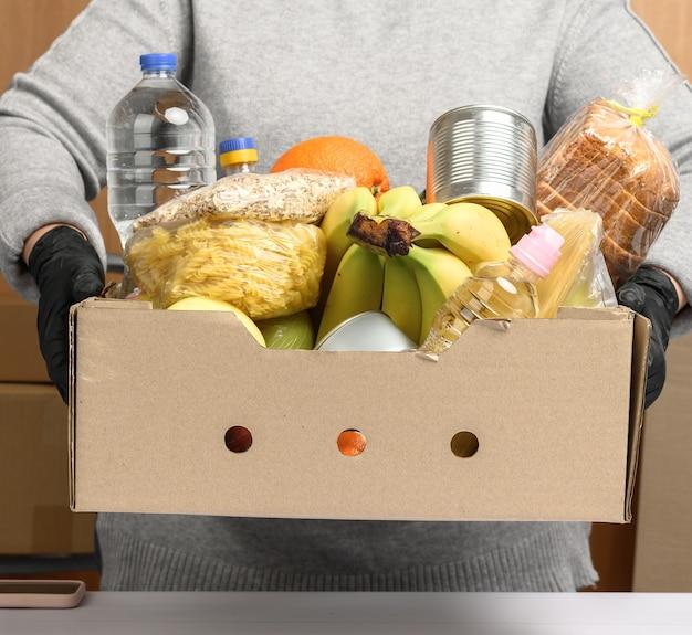 Mujer en suéter gris y guantes negros sosteniendo una caja de cartón con comestibles, concepto de asistencia y voluntariado, entrega de alimentos