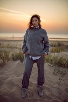 Mujer en un suéter gris y pantalones de pie en la playa con botas al atardecer por la hierba