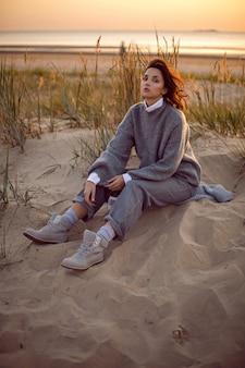 Mujer con un suéter gris y pantalones se sienta en la playa con botas al atardecer por la hierba