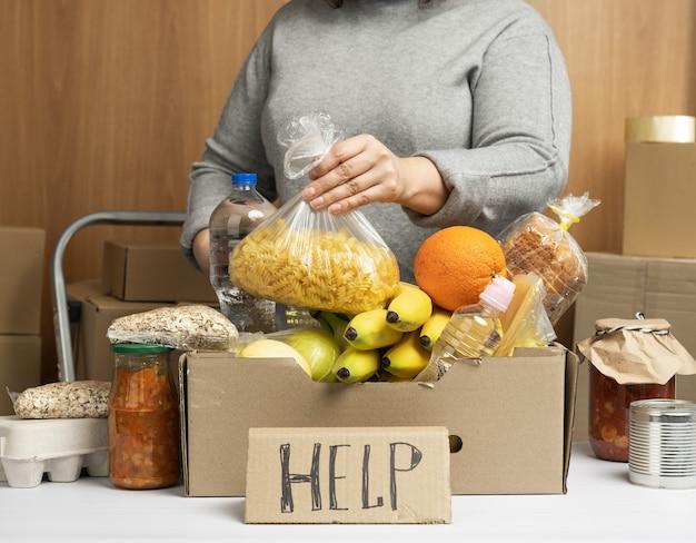Mujer con un suéter gris pone en una caja de cartón varios alimentos, frutas, pastas, aceite de girasol en una botella de plástico y conservas. concepto de donación y voluntariado