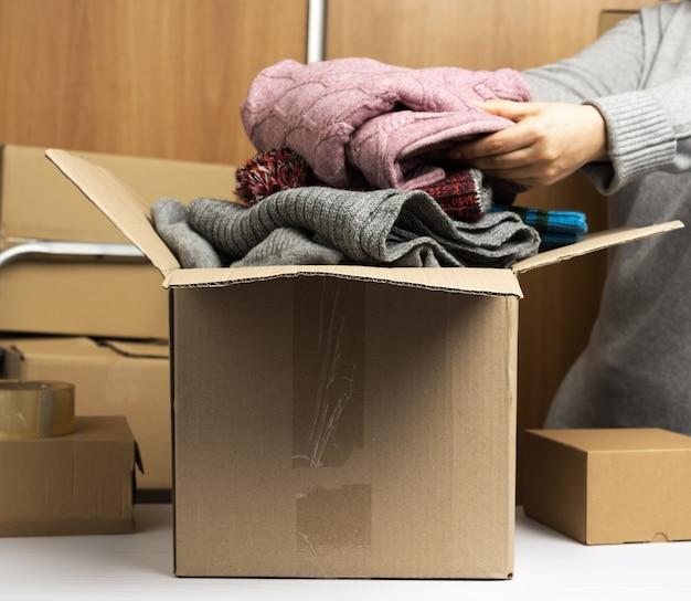 Mujer con un suéter gris recoge ropa en una caja, concepto de asistencia y voluntariado, mudanza. detrás de una pila de cajas marrones