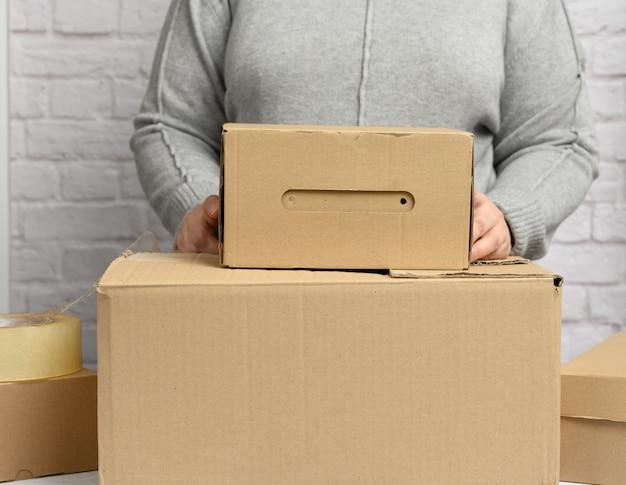 Mujer con un suéter gris sosteniendo una caja de cartón marrón, mudanza, donación