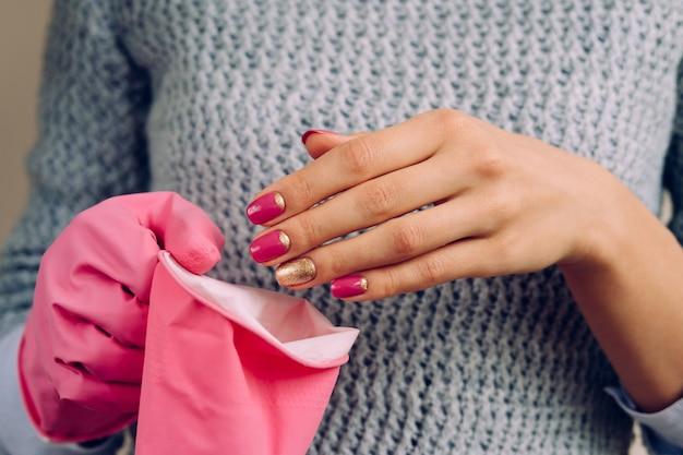 Mujer en el suéter gris usa guantes de goma rosa para la limpieza