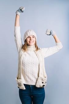 Mujer en suéter levantando las manos