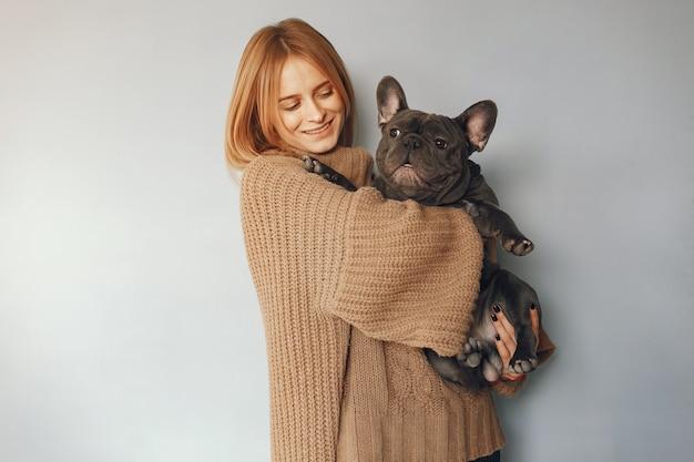 Mujer en un suéter marrón con bulldog negro